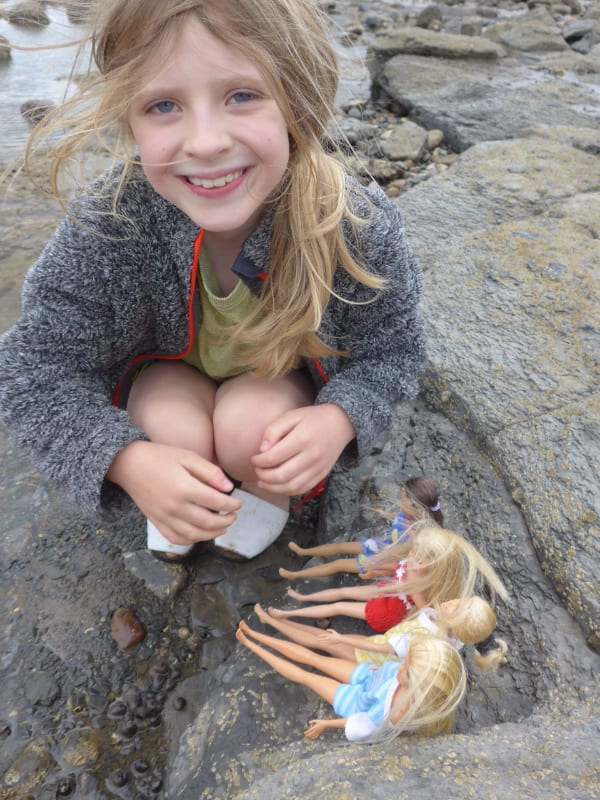 Child with dolls on Whitby beach