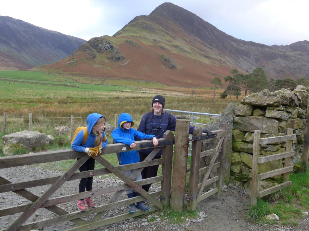 Family stands behind a gate, with the Keswick mountains in the background