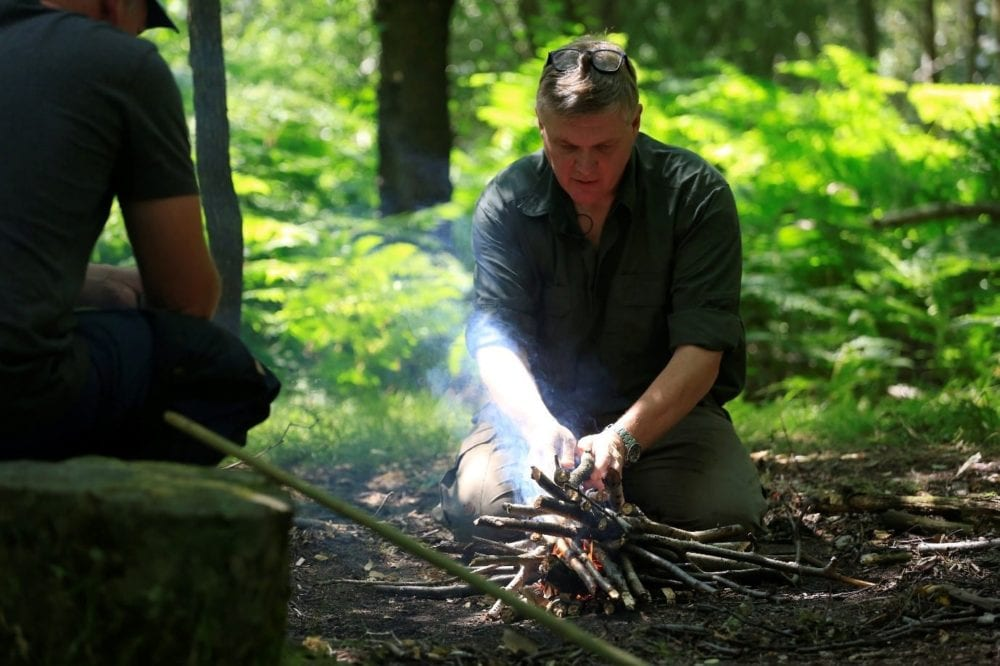 Ray Mears building a campfire in the woods