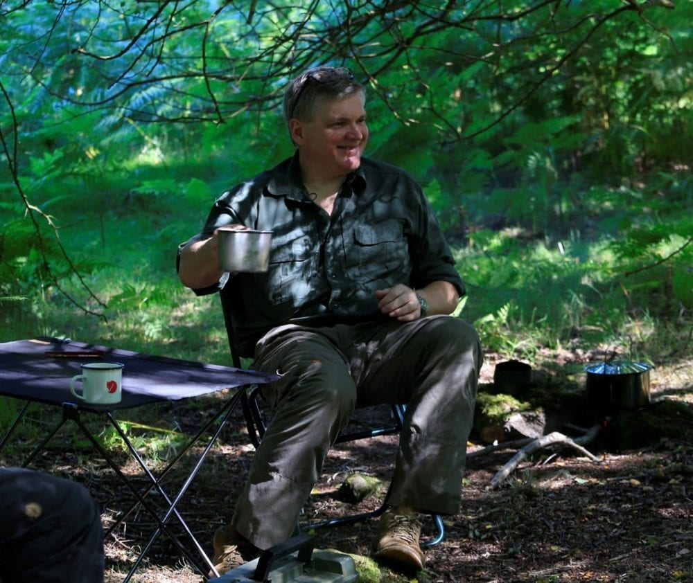 Ray Mears sitting in the woods smiling and holding a metal cup