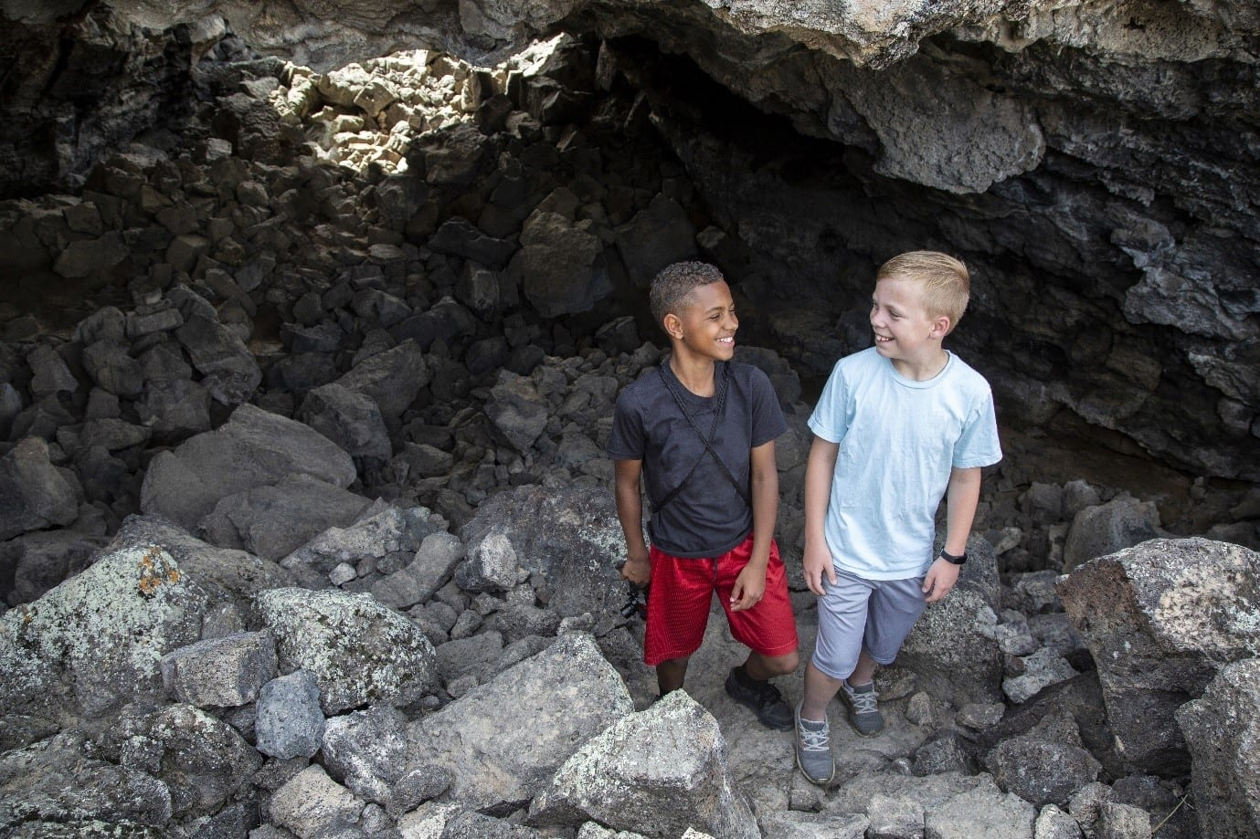 Two boys exploring a cave