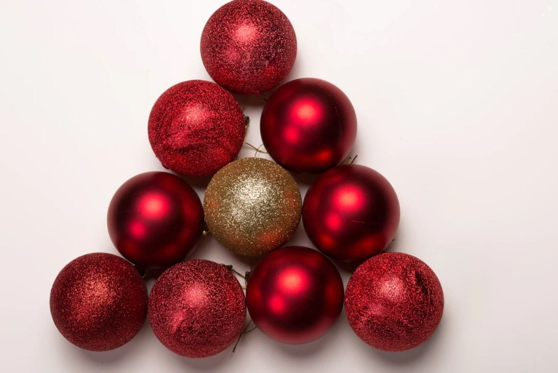Stack of red Christmas baubles with a gold bauble in the middle