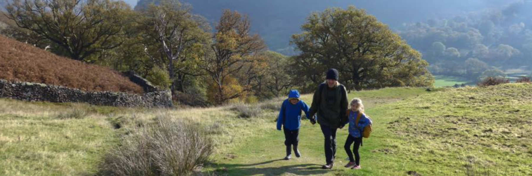 father_and_two_children_walking_up_hill
