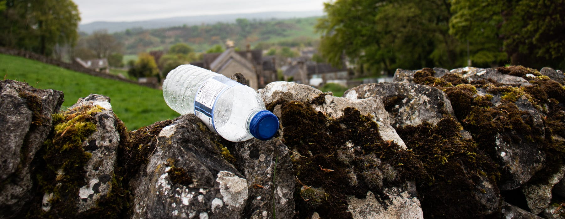 Plastic bottle on wall in countryside