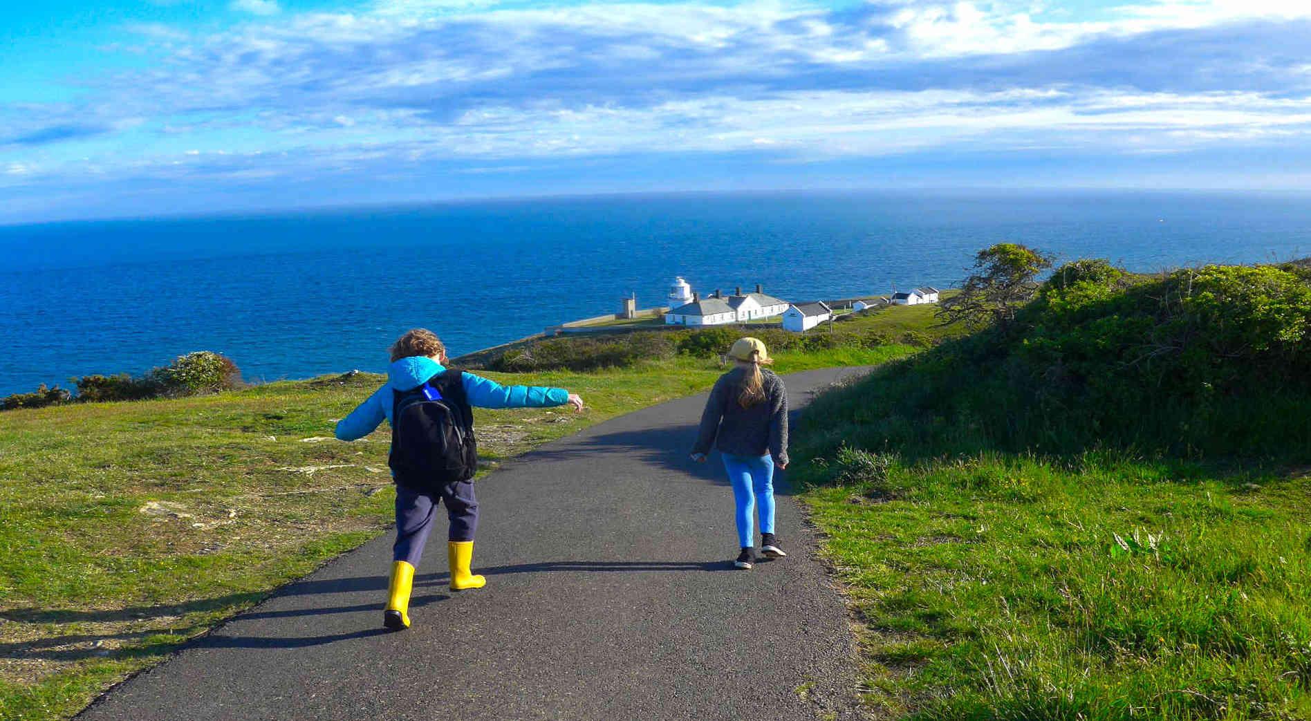 two_children_walking_near_lighthouse