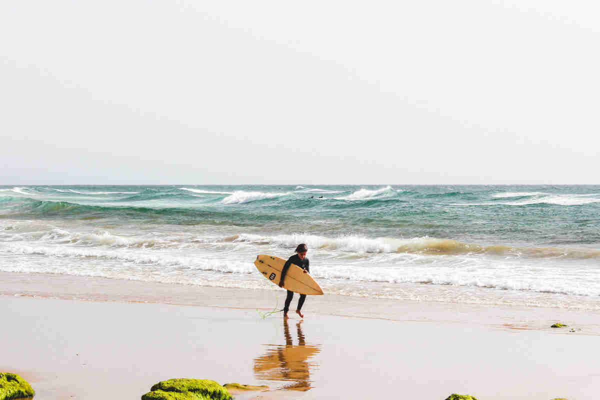 Boy surfing on the beach in Cornwall