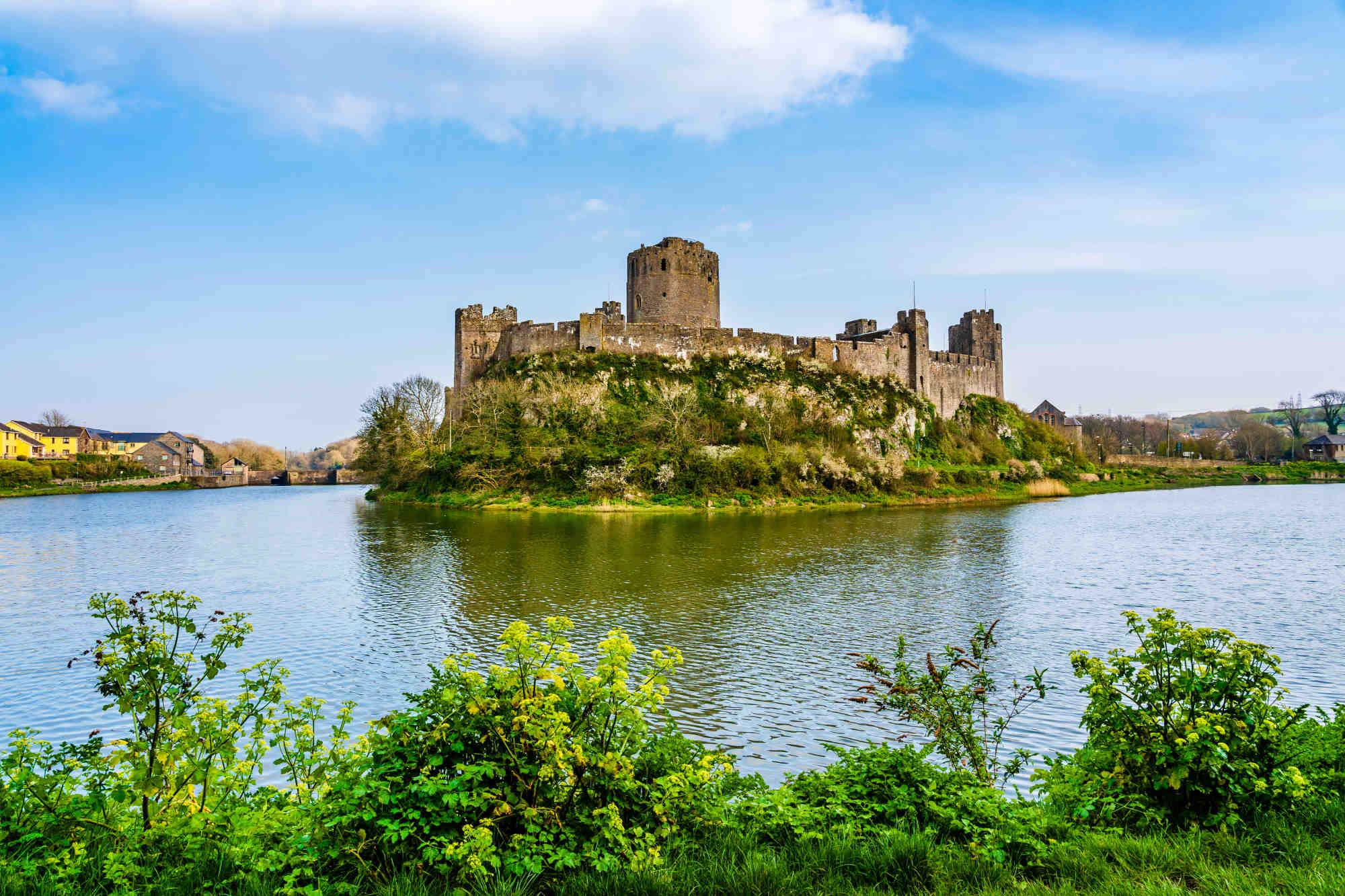 Pembroke Castle surrounded by a lake in Pembroke, Wales, UK