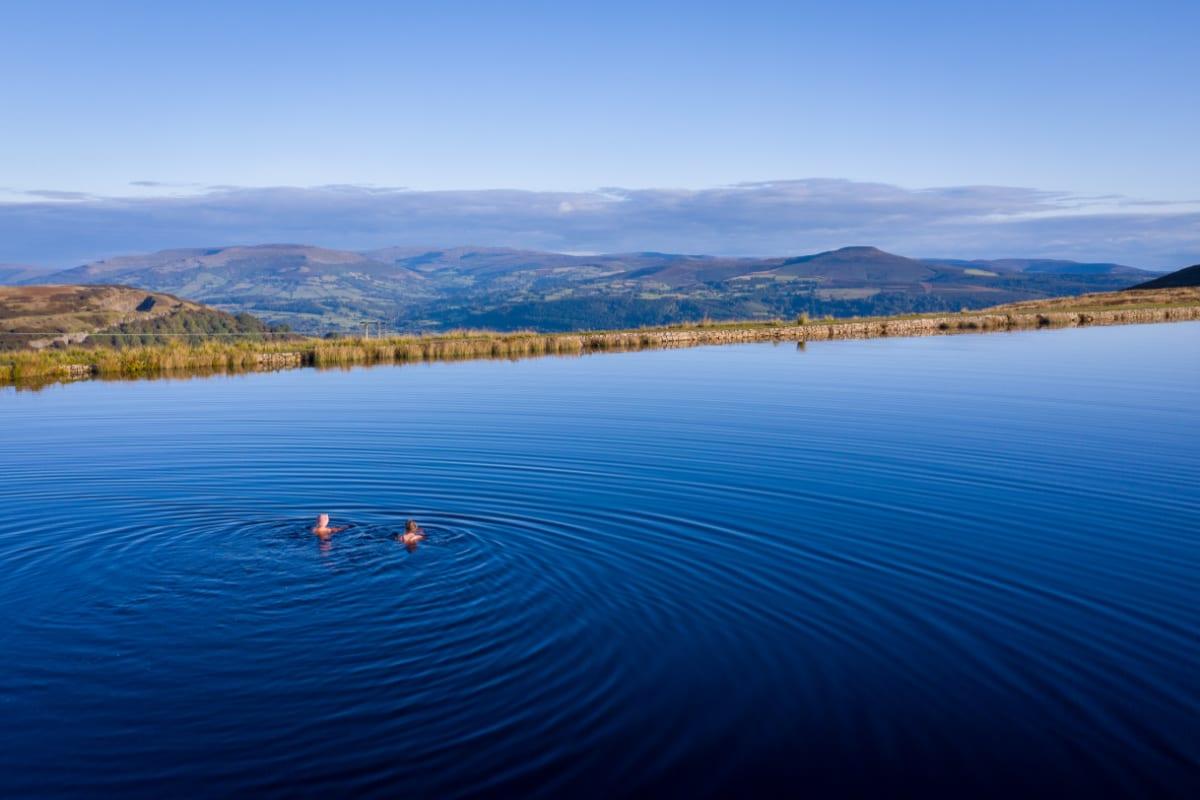 Two women wild swimming in a lake