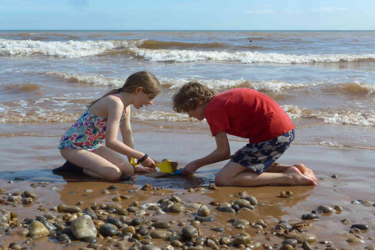 Boy and girl building a sandcastle on the beach