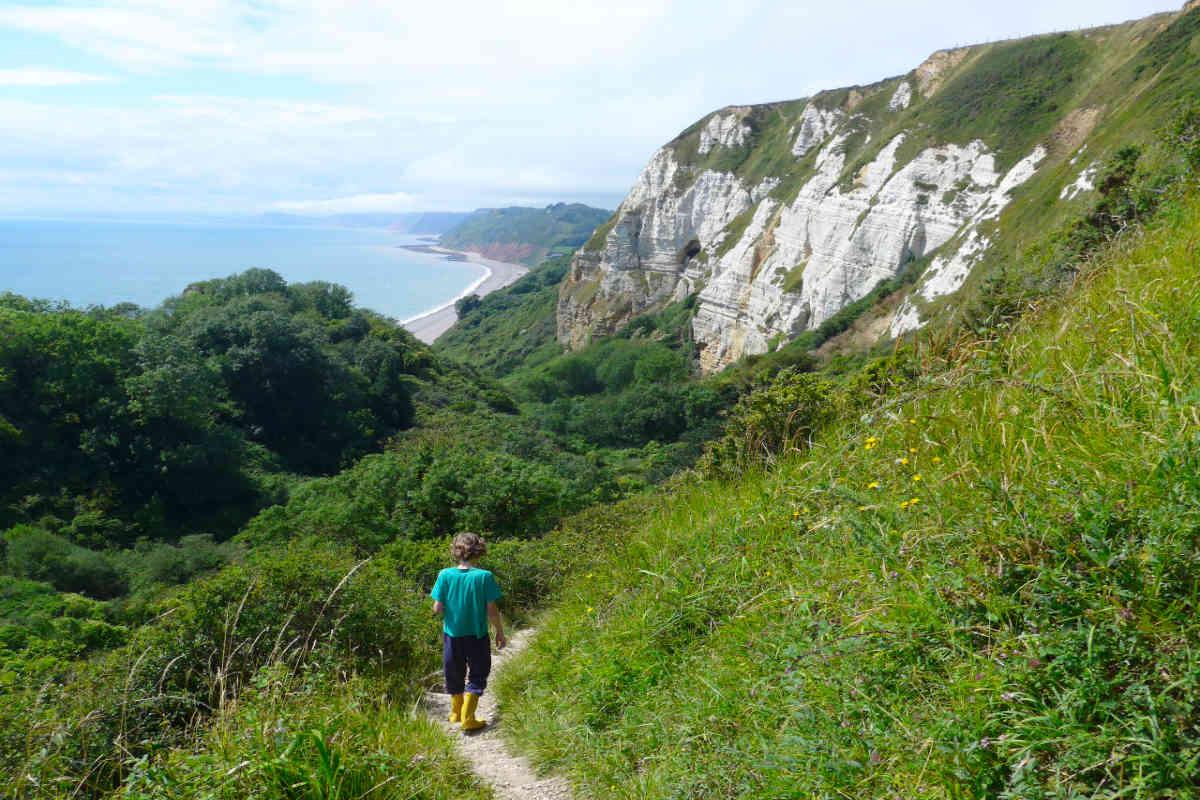Boy walking down a coastal path in Devon