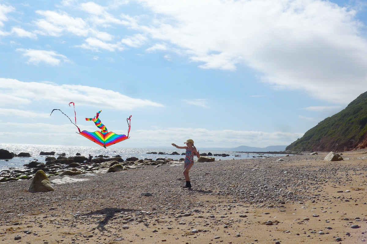 A girl flying a kite on the beach